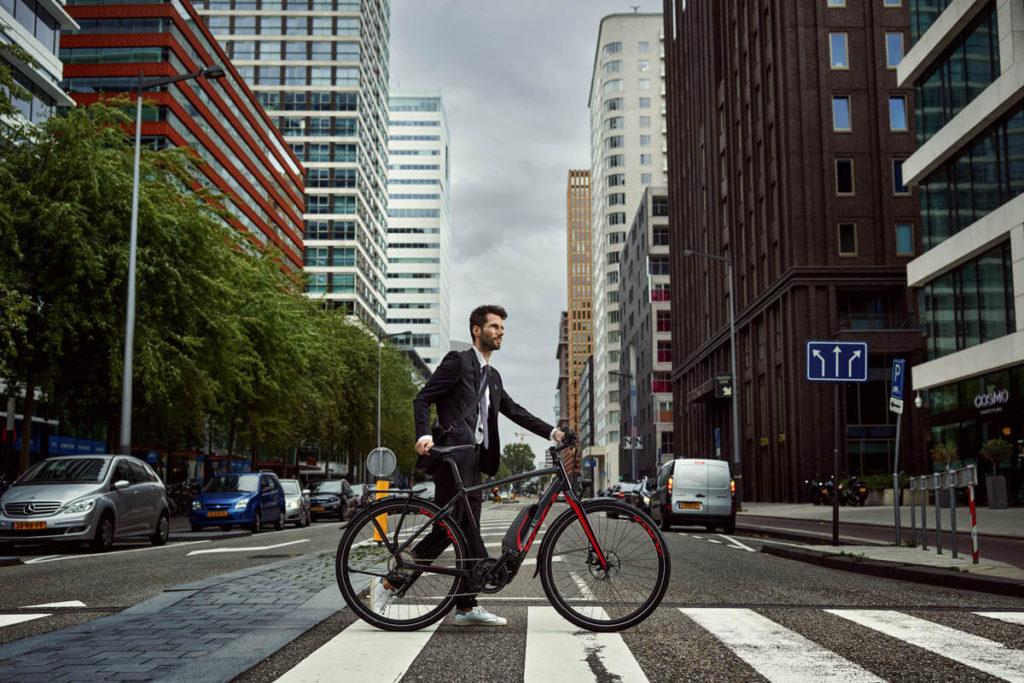 Mann schiebt ein E-Bike über einen Zebrastreifen